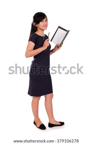 Full length portrait of friendly Asian school teacher holding a notebook and pen, isolated on white background - stock photo