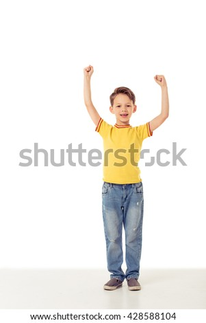 Full length portrait of funny little boy keeping hands in fists up, looking at camera and smiling, isolated on a white background - stock photo