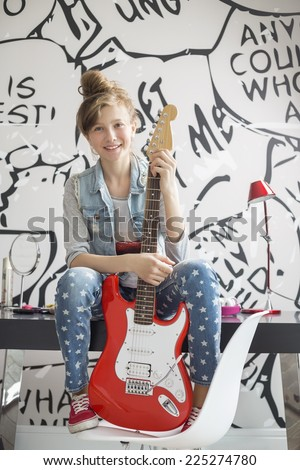 Full-length portrait of girl with electric guitar sitting on study table at home - stock photo