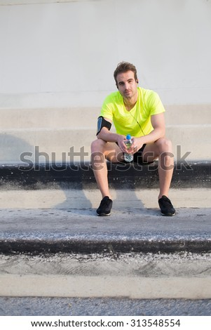 Full length portrait of handsome caucasian man with bottle of water in the hands having a rest after workout training outdoors, young male runner looking satisfied doing sports and listening to music - stock photo