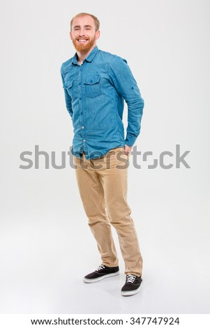Full length portrait of handsome cheerful young bearded man standing and smiling isolated over white background - stock photo