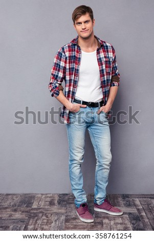 Full length portrait of handsome confident young man in checkered shirt standing over grey background - stock photo
