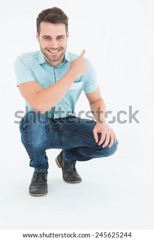 Full length portrait of handsome delivery man crouching while pointing backward on white background - stock photo