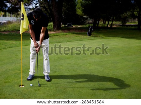 Full length portrait of handsome golfer man in white pants and black t-shirt standing on golf course preparing to hit golf ball, good golf game at sunny day