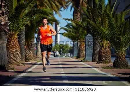 Full length portrait of handsome male runner jogging fast in tropic urban setting, muscular build man working out outdoors at sunny afternoon with copy space area for text message or advertise content - stock photo