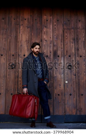 Full length portrait of handsome man holding vintage suitcase in hand while waiting for taxi car outdoors, fashionable bearded male with red travel bag posing while standing against wooden background - stock photo