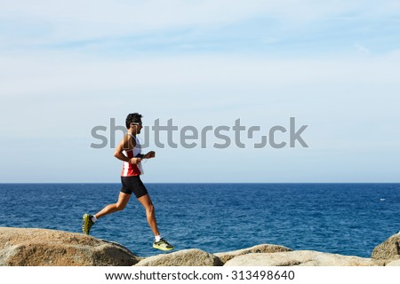 Full length portrait of handsome mature sports man running along the seashore while listening to music in headphones, male jogger while jumping over sea rocks while training hard outdoors in sunny day - stock photo