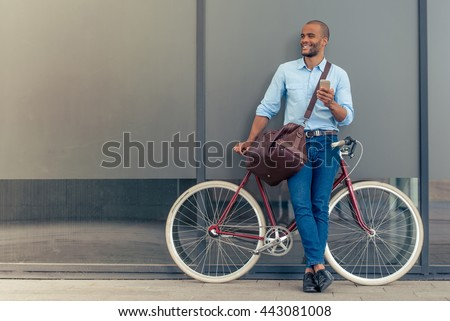 Full length portrait of handsome young Afro American man in casual clothes using phone, looking away and smiling while leaning on his bike, standing outdoors - stock photo