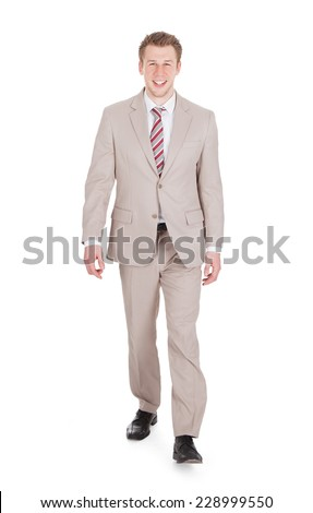 Full length portrait of handsome young businessman walking against white background - stock photo
