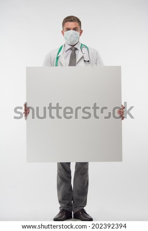Full length portrait of handsome young doctor in the gauze bandage, holding a big sheet of paper. Isolated on the white background - stock photo