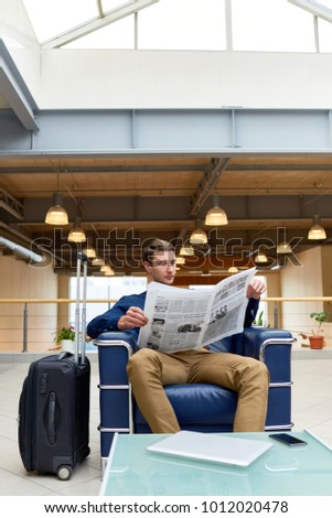 Full length portrait of handsome young man with suitcase reading newspaper sitting in leather armchair while waiting for check in in modem hotel
