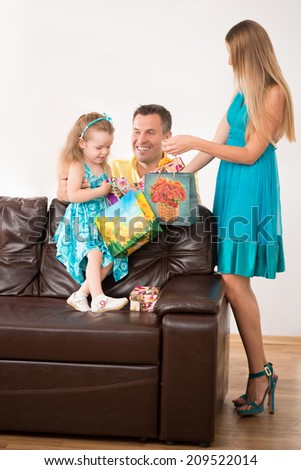 Full length portrait of happy adorable Caucasian family, little daughter and beautiful blonde mother looking into present package, smiling father hugging girl, at home - stock photo
