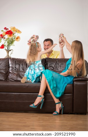 Full length portrait of happy adorable Caucasian family with little girl, father and daughter having fun with present, beautiful mother smiling, at home - stock photo
