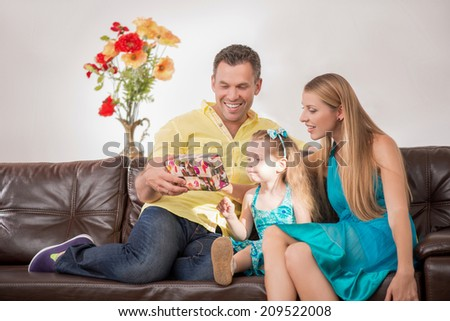 Full length portrait of happy adorable Caucasian family with little girl, father showing a present to cute daughter, beautiful mother smiling, at home - stock photo