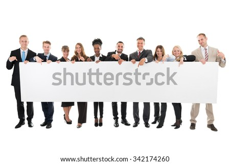 Full length portrait of happy business team pointing at blank billboard against white background - stock photo