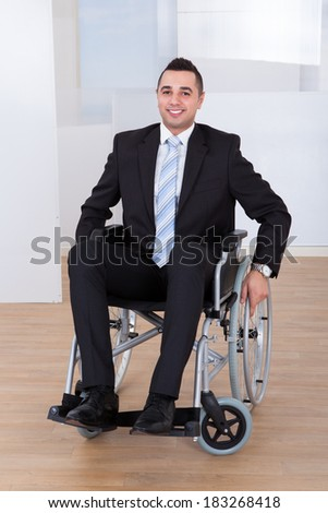 Full length portrait of happy businessman in wheelchair at office - stock photo