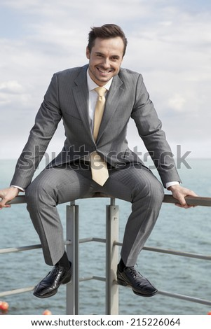 Full-length portrait of happy businessman sitting on terrace railings - stock photo