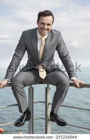 Full-length portrait of happy businessman sitting on terrace railings - stock photo
