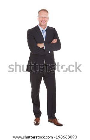 Full length portrait of happy businessman standing arms crossed isolated over white background - stock photo