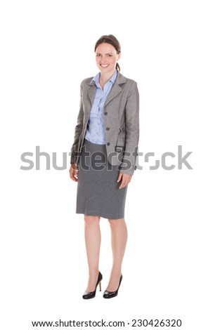 Full length portrait of happy businesswoman standing isolated over white background - stock photo