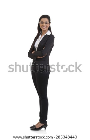 Full length portrait of happy businesswoman with arms crossed standing against white background - stock photo