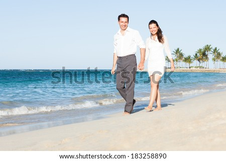 Full length portrait of happy couple holding hands while walking on beach - stock photo