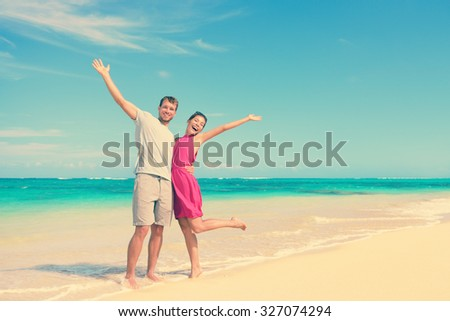 Full length portrait of happy couple with arms raised standing on shore. Joyful partners are enjoying at beach. Carefree tourists are celebrating summer vacation in idyllic nature. - stock photo
