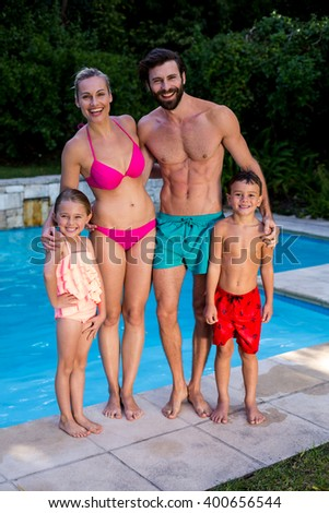 Full length portrait of happy family standing at poolside - stock photo