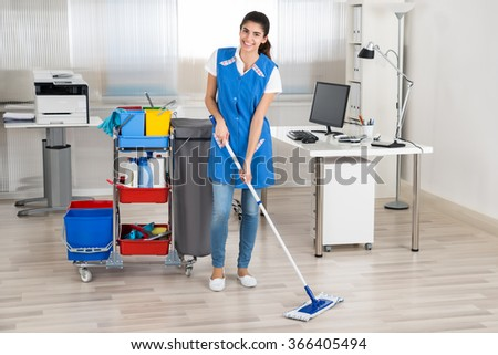 Full length portrait of happy female janitor mopping floor in office - stock photo