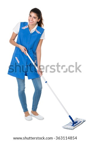 Full length portrait of happy female janitor mopping on white background - stock photo