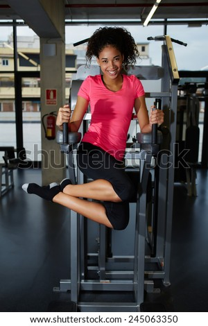 Full length portrait of happy fit woman exercising her abdominal muscles for beautiful figure - stock photo