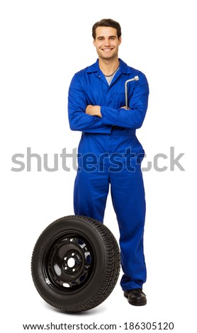 Full length portrait of happy male mechanic with spare tire over white background. Vertical shot.