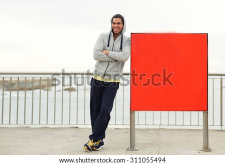 Full length portrait of happy male runner resting after morning jog while leaning on advertising board background with copy space area for text message or content,athlete having a break after exercise - stock photo