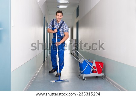 Full length portrait of happy male worker with broom cleaning office corridor - stock photo