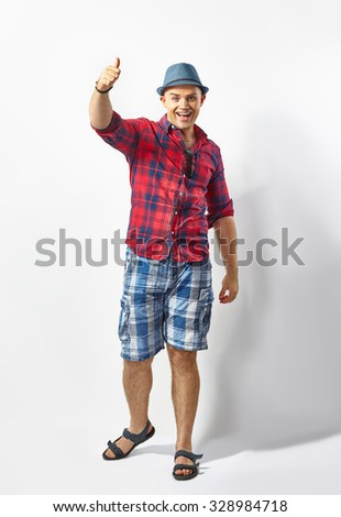 Full length portrait of happy man giving thumbs up sign - stock photo