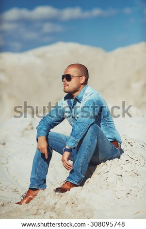 Full length portrait of happy man on a background of sand