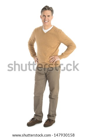 Full length portrait of happy man standing with hand on hips isolated over white background - stock photo