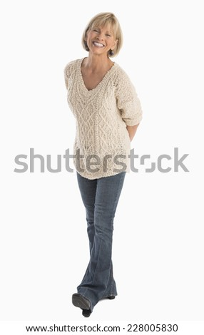 Full length portrait of happy mature woman with hands behind back walking over white background - stock photo