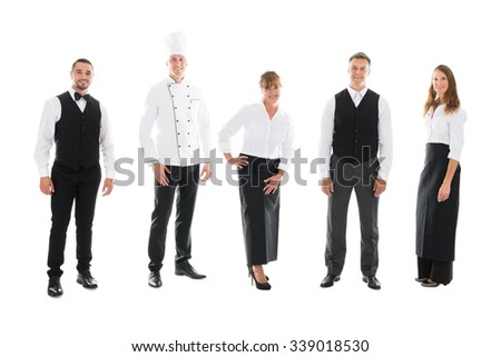 Full length portrait of happy restaurant staff standing over white background - stock photo
