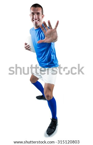 Full length portrait of happy rugby player defending against white background