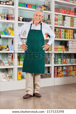 Full length portrait of happy senior male owner standing with hands on hips in supermarket