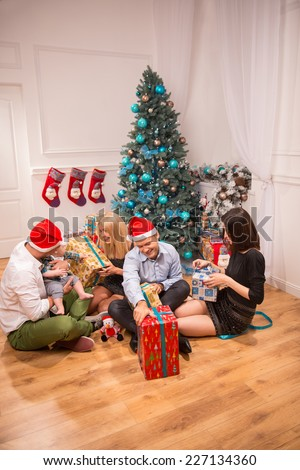 Full-length portrait of happy smiling company of friends sitting on the floor in the light beautiful room near the Christmas tree unpacking their presents - stock photo
