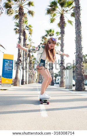 Full length portrait of happy smiling woman with trendy look rejoice while skating on penny board on tropical curb during summer weekend, cheerful female skateboarder riding on long board having fun - stock photo
