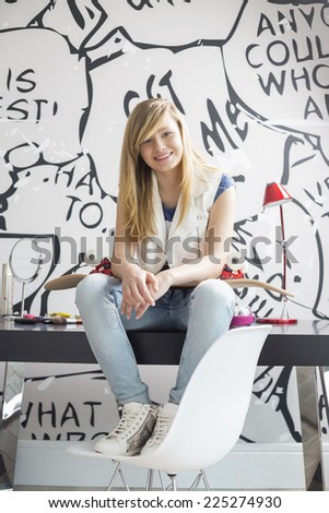 Full-length portrait of happy teenage girl with skateboard sitting on study table at home - stock photo