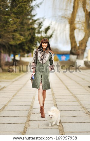 Full length portrait of happy woman walking with her little dog - outdoor  - stock photo