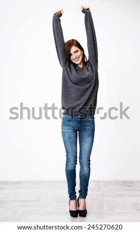 Full length portrait of happy woman with raised hands up - stock photo