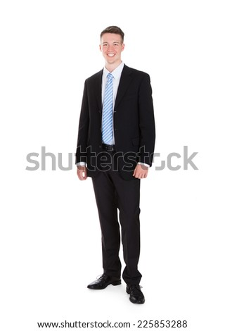 Full length portrait of happy young businessman standing isolated over white background - stock photo