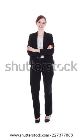 Full length portrait of happy young businesswoman standing arms crossed over white background - stock photo