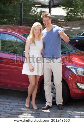Full length portrait of happy young couple holding key by new car