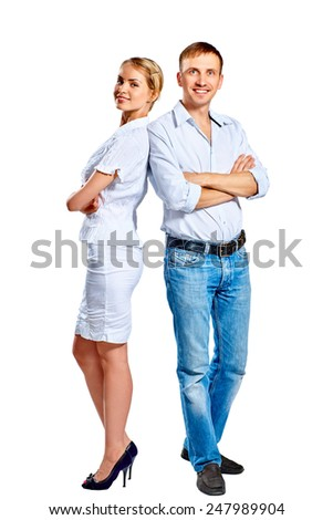 Full length portrait of happy young couple standing back to back isolated on a white background - stock photo